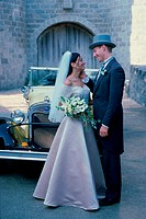 Newlywed couple standing in front of an antique car