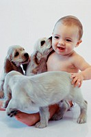 Baby boy playing with puppies