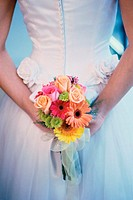 Mid section view of a bride hiding a bouquet of flowers