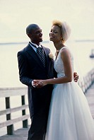Newlywed couple embracing on a pier