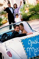 Portrait of a bride and her groom sitting in a convertible car