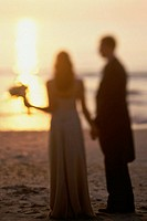 Newlywed couple standing on the beach