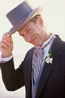 Portrait of a groom wearing a hat smiling