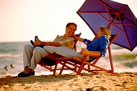 Mid adult couple sitting on lounge chairs on the beach (thumbnail)