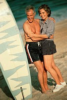 Senior couple embracing each other on the beach standing beside a surfboard