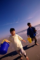 Two boys running with sand pails on the beach