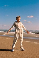 Senior woman exercising on the beach (thumbnail)