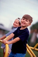 Portrait of two boys standing on a merry-go-round