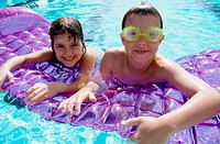 Portrait of a boy and a girl leaning on a pool raft (thumbnail)