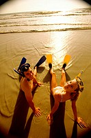 High angle view of a teenage couple sitting on the beach wearing snorkels and flippers
