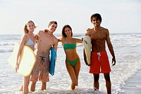 Portrait of two teenage couples standing on the beach holding boogie boards (thumbnail)