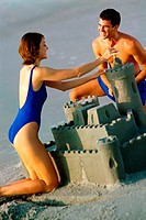 Young couple making a sand castle on the beach