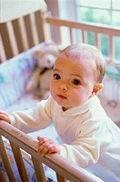 Baby boy standing in a crib (thumbnail)