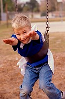 Portrait of a boy hanging on a swing