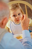 Grandfather feeding his granddaughter (thumbnail)