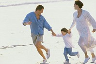 Parents running on the beach with their daughter