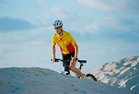 Young woman cycling on sand