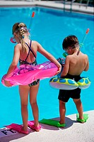 Rear view of a boy and a girl standing at the poolside wearing snorkels and flippers