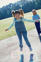 Two girls playing hopscotch