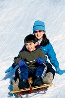 Boy and a girl riding a sled