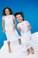 Portrait of two girls jumping on a bed