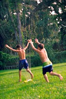 Rear view of two boys playing under a water sprinkler