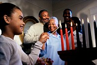 Girl lighting candles to celebrate Kwanzaa