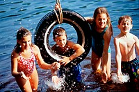 Group of children playing on a tire swing