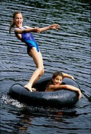 Portrait of two girls playing in water with inner tube