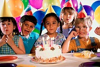 Group of children in front of a birthday cake at a birthday party
