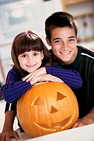 Boy and a girl smiling next to a jack-o-lantern