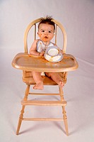 Portrait of a baby boy sitting in a high chair playing with a bowl