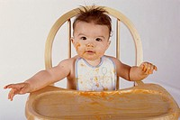 Portrait of a baby boy sitting in a high chair
