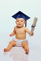 Baby boy wearing a mortar board holding a diploma