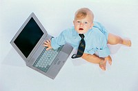 Portrait of a baby boy touching a laptop