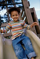 Portrait of a girl sliding down a slide