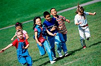 Group of children running on a lawn