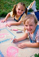 Portrait of two girls drawing on the ground with chalk