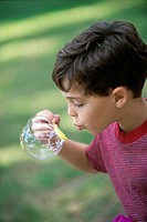 Side profile of a boy blowing bubbles
