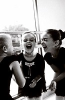 Three ballerinas laughing