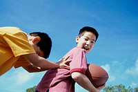 Low angle view of two boys playing with a football