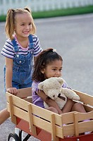 Two girls playing with a push cart