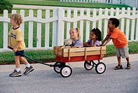 Side profile of two boys and two girls playing with a push cart