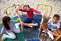 High angle view of three girls playing on a merry-go-round