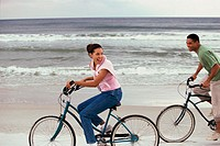 Side profile of a young couple cycling on the beach