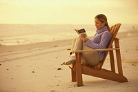 Side profile of a young woman reading a book on the beach
