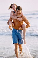 Young woman riding piggyback on a young man on the beach