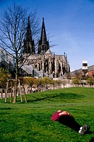 Man resting on a lawn, the cathedral (dom) at back. Cologne (Köln). Germany