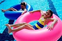 High angle view of a boy and a girl lying on inflatable rings in a swimming pool