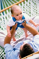 Father lying in a hammock playing with his baby boy